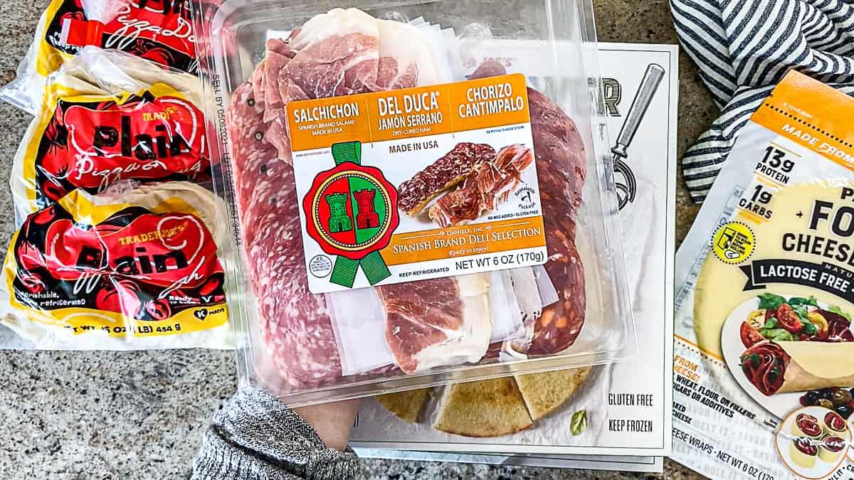 Top down shot of Trader Joe's charcuterie Spanish meat tray with Salchichon Salame salami, Jamon Serrano ham, Chorizo Cantimpalo.