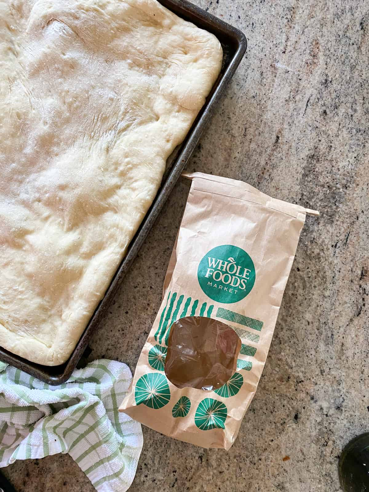 Top down shot of a bag of whole foods pizza dough next to parbaked pizza crust.