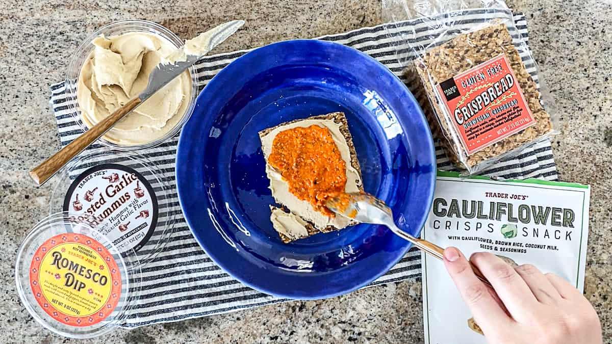 Top down shot of vegan trader joe's gluten free snacks idea with premade humus and crackers.