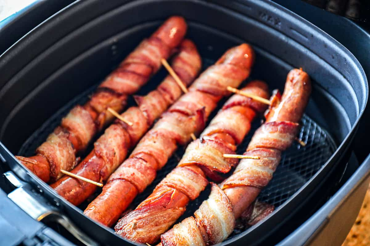 Closeup shot of Air Fryer Bacon Wrapped Hot Dogs with toothpicks.