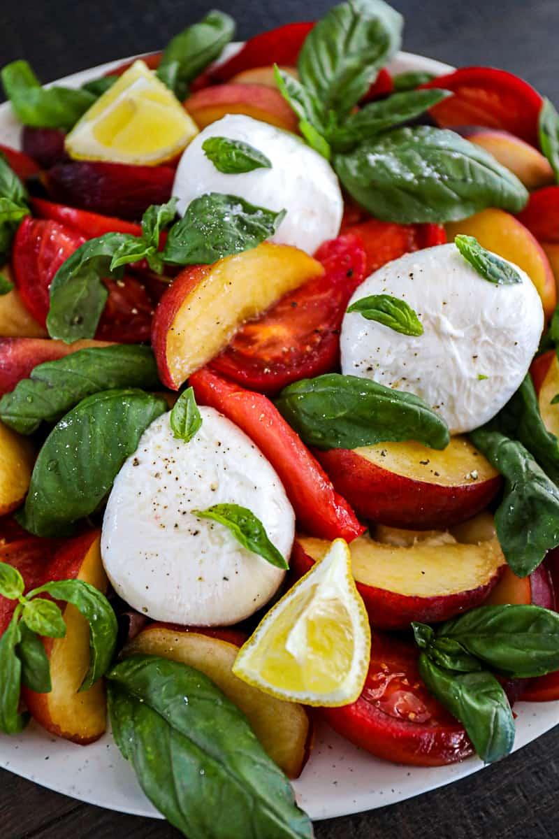 Closeup of Fresh Peach Salad with Burrata And Tomatoes.