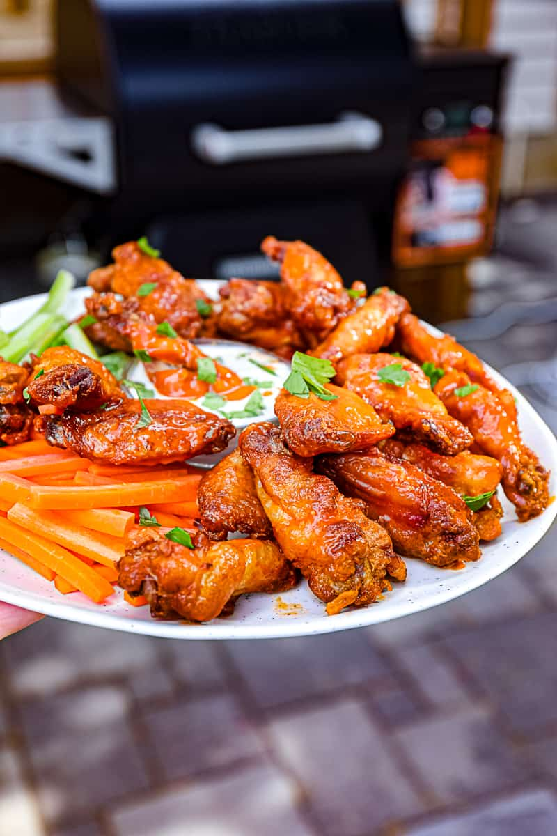 Closeup of smoked wings with Traeger smoking food in the background Sip Bite Go