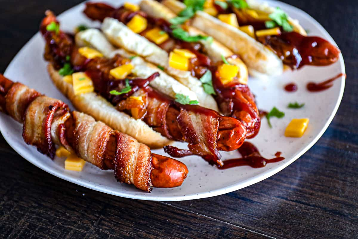 Cooked Bacon Wrapped Hot Dogs with cheddar cheese and bbq sauce.