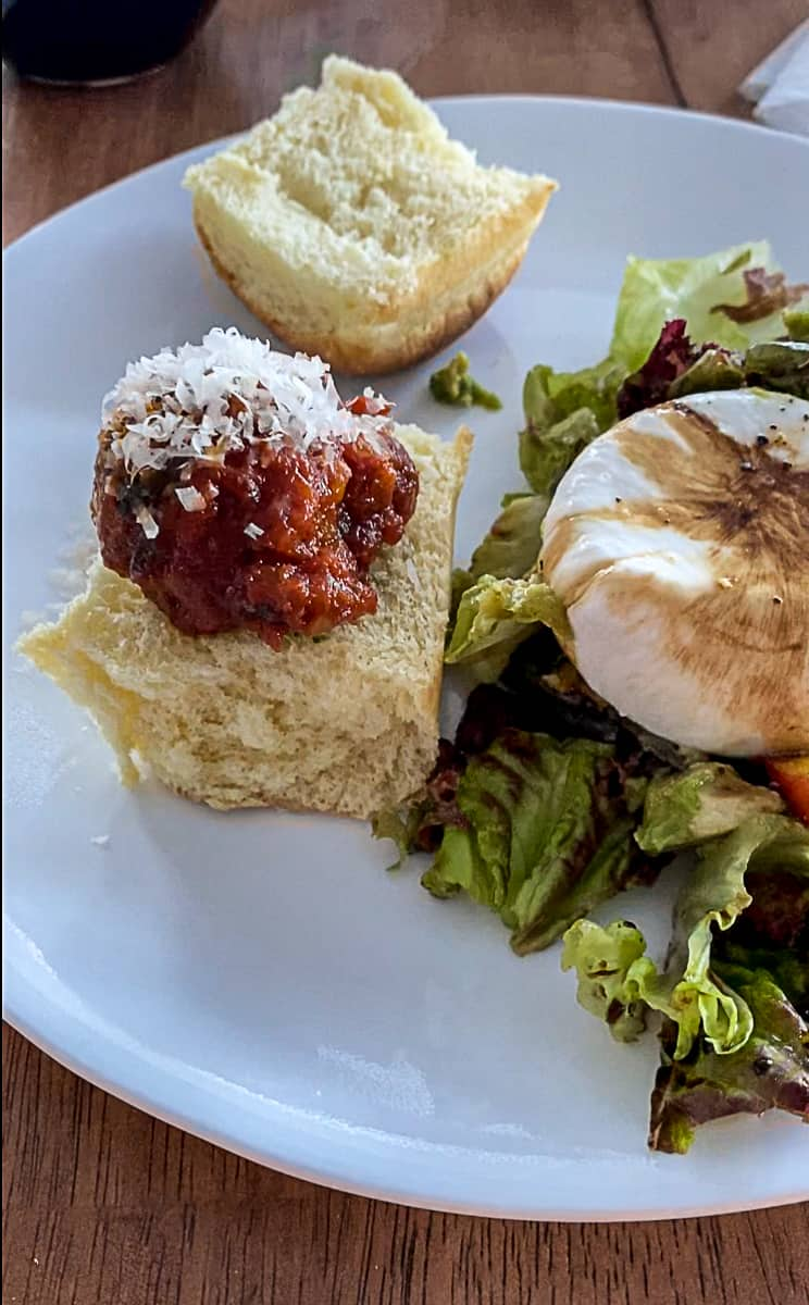 Easy slow cooker dinner Hawaiian Roll Meatball Slider on a plate with salad.
