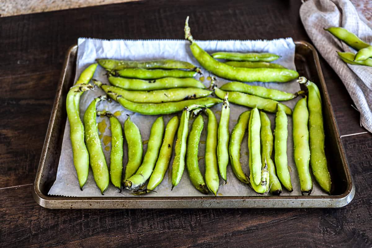 Fresh Fava Bean Pods seasoned on a sheet tray
