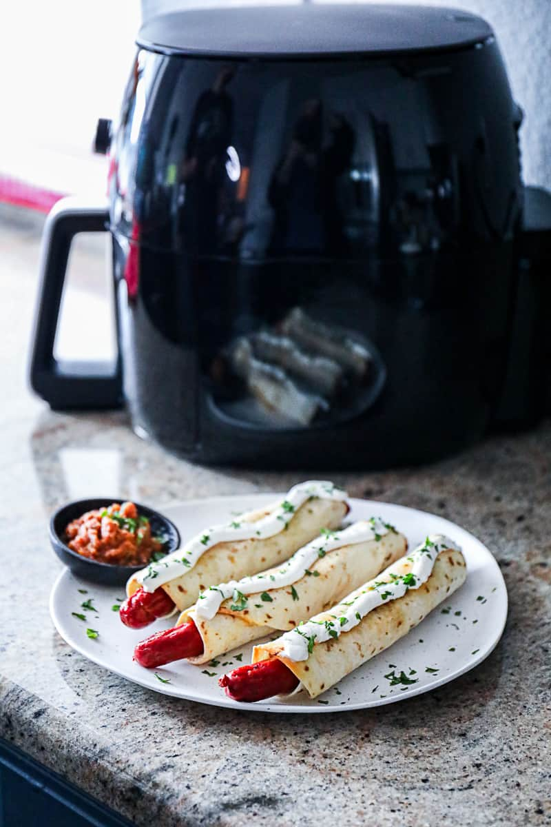 Frozen foods in air fryer example with hot dogs.