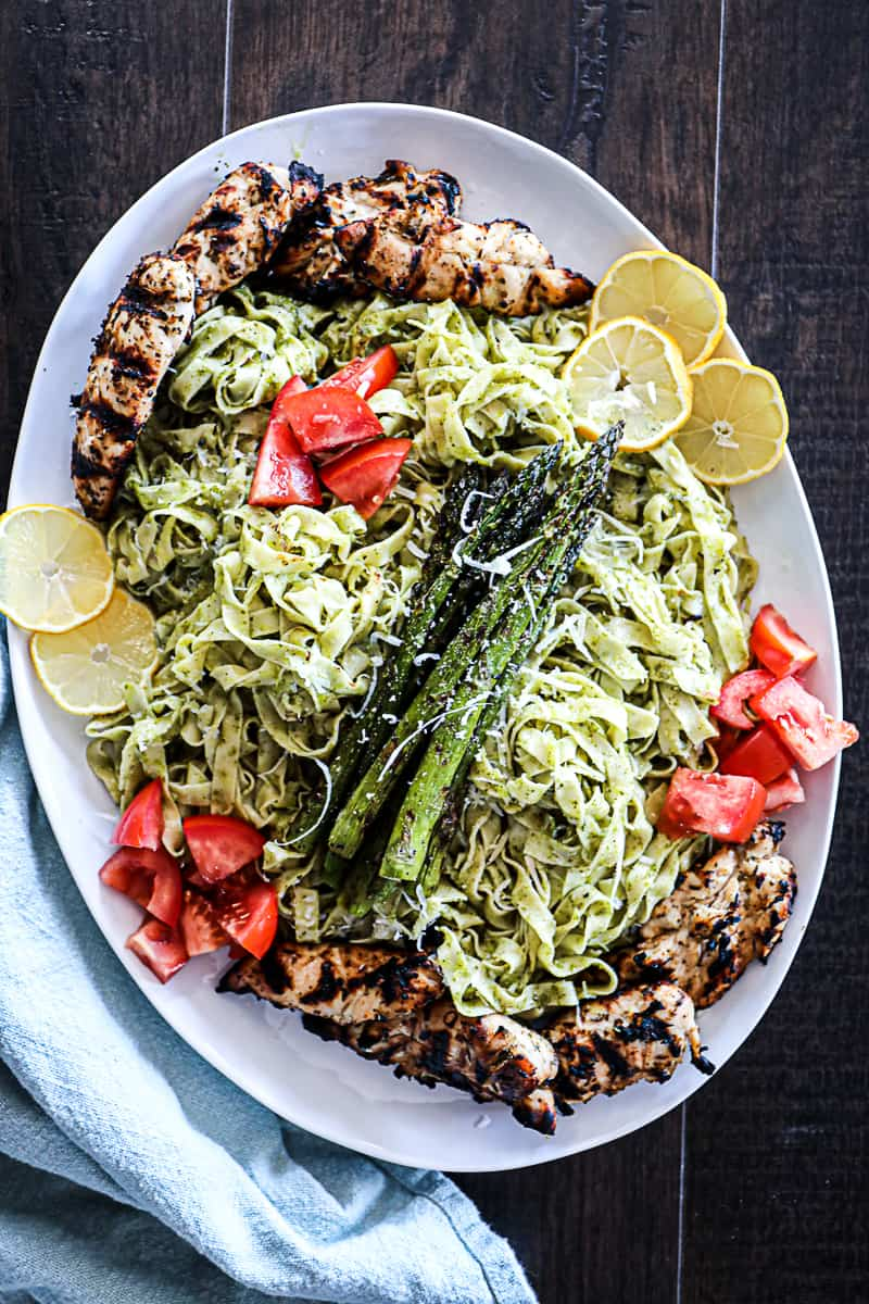 Platter with family style Pesto Pasta with chicken and asparagus and tomatoes and lemon.
