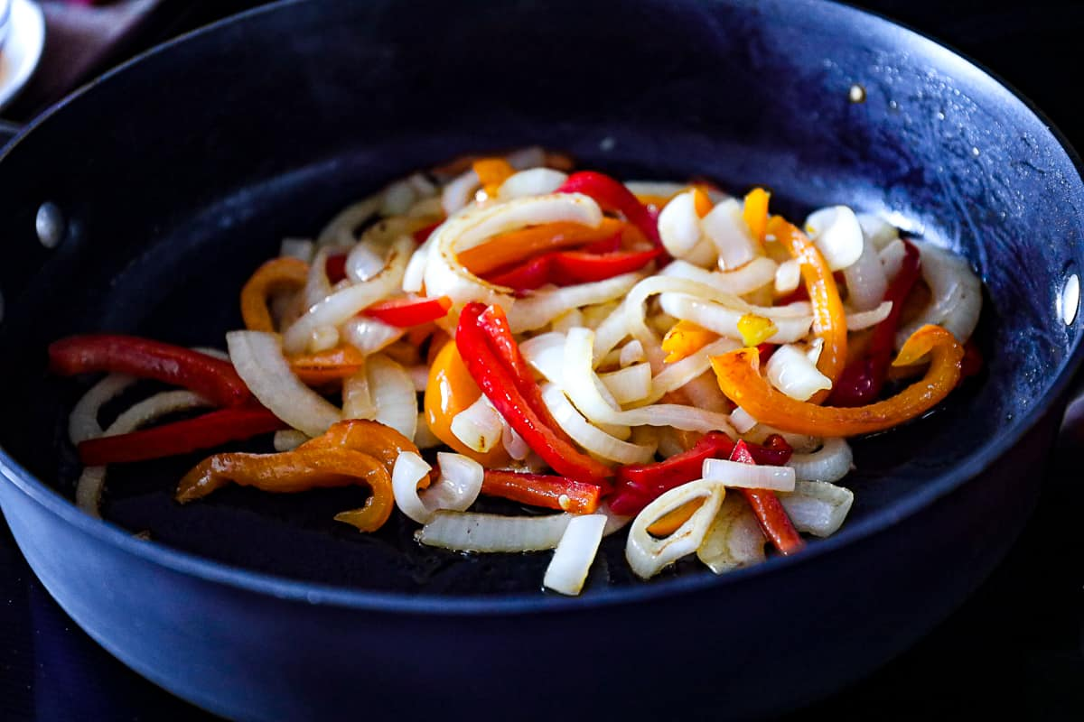 Sautéed onions and peppers in a pan for pork pasta.