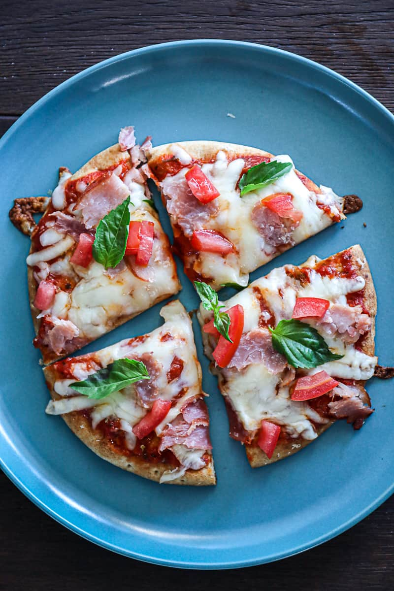 Italian Pita Pizza with cheese and ham and fresh basil leaves.