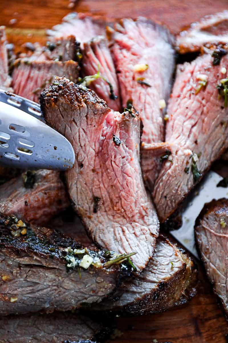 Thinly cut tri tip steak against the grain